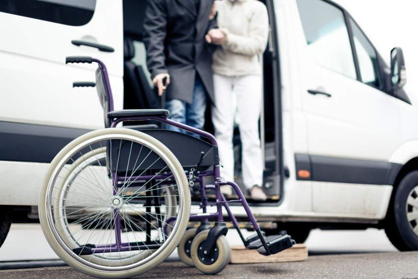 Rollstuhl vor Fahrzeug - bildlich für Vorsorge in der Rentenberatung und Versicherungsberatung